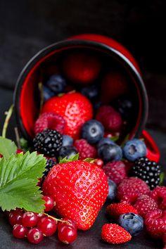 Fresh berries falling out of red cup on black background, low key by Anastasy Yarmolovich #AnastasyYarmolovichFineArtPhotography  #ArtForHome #Food