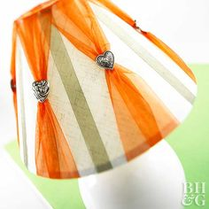 Sheer ribbons and shank buttons are perfect additions to a dull lampshade. Hot-glue the ends of thin opaque ribbon lengths to the inside of a lampshade. Hot-glue one end of wide sheer ribbon to the top of the shade. Slide a button shank up to the middle of each length of ribbon; fan out the bottom of the ribbon before gluing it in place.