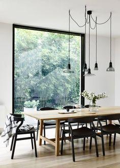 Salle à manger avec une grande baie vitrée sur l'extérieur. Belle série de suspensions.