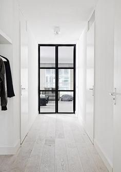 Steel door.  White walls.  White wash floors.