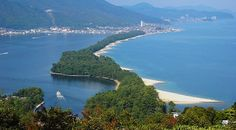 """Amanohashidate (天橋立) is a pine covered sandbar that spans the mouth of Miyazu Bay in the scenic, coastal region of northern Kyoto Prefecture. Viewed from the mountains at either end of the bay, the Amanohashidate Sandbar (which roughly translates to """"bridge in heaven"""") looks like a pathway between heaven and earth. The scene has been admired for centuries and is ranked among Japan's three most scenic views."""