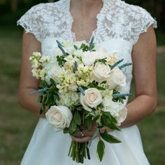 The bride's bouquet is elegant in shades of cream and off-white, with blue to give it some color. Comprised of roses and tuberoses, the bouquet also features hydrangeas and muscaris to complement the rustic feel of the wedding. Photo Credit: Joy Michelle Photography.