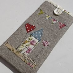 A pretty handmade linen case for your glasses.PLEASE NOTE THIS IS NO LONGER AVAILABLE FOR CHRISTMAS DELIVERY. ALL ORDERS WILL BE DISPATCHED IN JANUARY. Handmade with Irish linen and lined with rose covered cream fabric, this case features a lovely cottage scene complete with bunting. It has an added layer of fleece for extra protection in your handbag and is closed with a vintage button and cream ribbon loop. Would make a lovely gift for a friend or relative. There is a matching needle case…