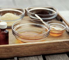 Glass bowls with various oils on a wooden tray outdoors  DIY USES FOR HOUSEHOLD FOODS