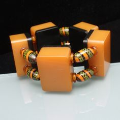This is a fabulous statement-making bracelet in Bakelite and Venetian glass. The Bakelite is butterscotch; backed with black. Swirled Venetian glass beads are positioned between the Bakelite pieces an