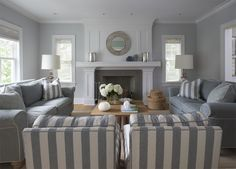 Beautiful blue monochromatic living room design with blue gray walls paint color, blue sofas with white piping, white & blue striped chairs, blue & white striped pillows, rectangular maple cocktail table, slate fireplace with chevron herringbone firebox, woven baskets and gray blue linen roman shades.