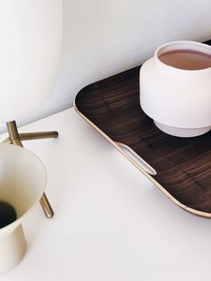 Dining room idea - use a wooden tray to bring warmth to a minimal dining room.#diningroomaccessories #woodtrayideas