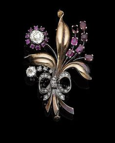 A ruby and diamond spray brooch, circa 1940 Modelled as a bouquet of flowers, set with oval-cut rubies, cushion-shaped and rose-cut diamonds, to polished leaves and a similarly-cut diamond tied ribbon