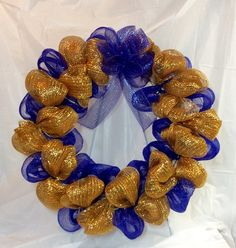 "Blue and gold mesh wreath. Royal blue and metallic gold mesh cover a 20""  box wire frame to make this 24"" wreath. Bright blue bow at top. by KhQualityCreations on Etsy"