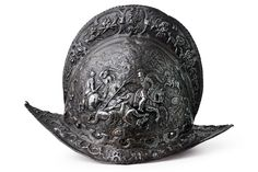 Iron skull in one piece, with average tall comb and boat-shaped brim, twisted border, small defects and parts missing, at the base a row of rivets (most of the missing). The entire surface is finely and majestically embossed with high and bas-relieved decorations, depicting a battle on horseback framed by grotesque masks and bands, on a side, and a group of warriors on horseback crossing a river on the other, framed en suite. North Italy  - late 16th Century.   CZERNY'S