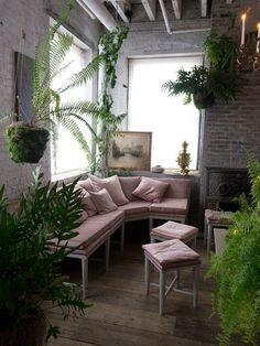 壁が石造りのリビングの隅に、グレイッシュピンクのソファーを置きます。植物を植えた鉢を上から吊るし、ツタが壁をつたい、ソファの後ろにある窓の前に絵を立てます。