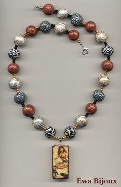 Collier avec pendentif synthétique et avec perles en pâte polymère.