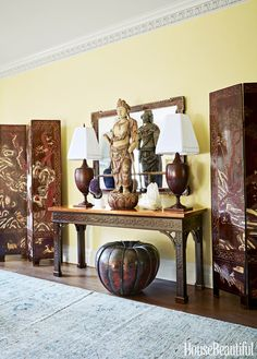 A custom Chippendale console holds an 1890s carved-wood Guanyin figure and urn-shaped lamps.