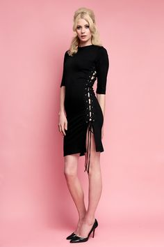 Update your Wheels Wardrobe with this seductive new style. Versatile yet daring, this figure hugging dress emphasises your silhouette with a flirtatious asymmetrical split down the side of the body, lacing up with plush black velvet ribbons and metal eyelets. Tailored to the curves of the figure, it is constructed in our classic stretch black matte ponti fabrication, also featuring a round neckline, ¾ sleeve and invisible zipper down the centre back. This season's must have s…