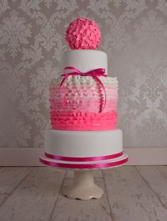 A 3 tier wedding cake with a double height middle tier covered in ombre ruffles and finished with a hydrangea pom pom.