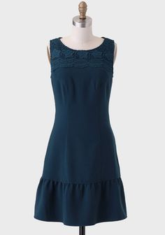 Adorned with crocheted lace across the neckline, this dark teal dress features a drop-waist ruffle and flattering front seams. Pair this elegant frock with classic pumps and sparkling accessories...