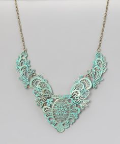Charming and inspired by a vintage sense of style, this hand-painted filigree necklace is a dreamy way to decorate the décolleté.Chain: 18'' longPendant: 4'' W x 5.7'' longBronze / brassMade in the USA