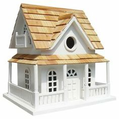 """Invite feathered residents to your garden or backyard with this charming birdhouse, featuring a coastal cottage-inspired silhouette and shingled roof.   Product: BirdhouseConstruction Material: WoodColor: WhiteFeatures:  Unpainted nest boxVentilation and drainage holes includedRemovable back wall for easy maintenance 1.25"""" Entry holeDimensions: 10.5"""" H x 10"""" W x 9"""" D"""