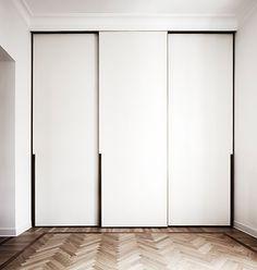Clean sleek look walk in closet with parquette