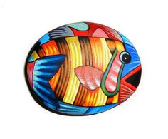 Painted stone colorful fish !  Is Painted with high quality Acrylic paints and finished with Glossy varnish protection.