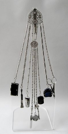 Chatelaine of polished steel ornamented with faceted steel beads, stamped on reverse of hook-plate, with ten writing and sewing implements suspended on nine chains. The needle-case contains an engraved bodkin. London ca. 1838