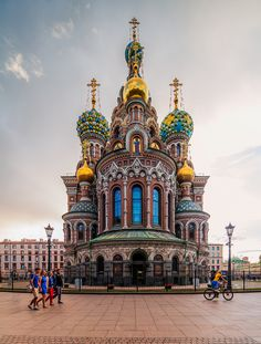 Tourists enjoy a view of one of the most popular attractions in St Petersburg - The Church of the Savior on Blood. Russia