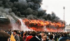 Bradford City's main stand burns while fans gather on the pitch at Valley Parade, where they had come to see their team celebrate promotion from the old Third Division.  1985