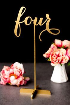 Gold table number in cursive calligraphy on high stand.