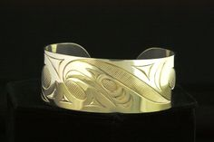 """A 1"""" wide bracelet with a carve eagle by Dylan Thomas. Contemporary coast salish style.  Northwest coast art and First Nations Art at Ahtsik Native Art Gallery."""