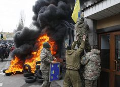 """Servicemen from the battalion """"Aydar"""" throw a Ukrainian flag from the building of Ukraine's Defence Ministry, during a protest against the disbanding of the battalion, in Kiev February 2, 2015. REUTERS/Valentyn Ogirenko"""