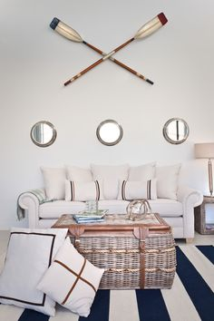 Clean, modern nautical style decoorating with porthole mirrors and paddles above sofa and blue and white striped rug.