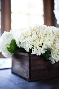 Half the centerpieces will be white reclaimed wood boxes filled with coral hydrangea and green leaves surrounded by mercury glass votives