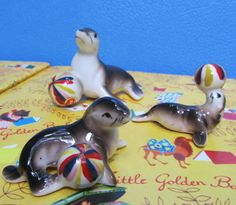 Sea Lion Figurine Miniature Set Ceramic Seal Animal Family with Ball  We love this playful family of sea lions!  Great details on these bone china miniatures!  All are in good condition, Papa has a slight indent on his head, probably from the manufacturing process.  Two of the three have their original S.S. Japan stickers intact.  Lots of decorating opportunities with this fun group!  We estimate that they are from the 50s.  Approximate sizes:  Papa 1 3/4 tall, 3 long Mama 1 tall, 2 long...