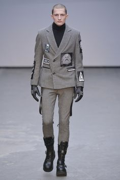 Anarchic graphics badges on military-style tailoring from KTZ at London Collections: Men.