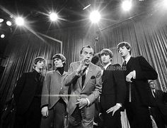 """Ed Sullivan, center, stands with The Beatles during a rehearsal for the British group's first American appearance, on the """"Ed Sullivan Show,"""" in New York on Feb. 8, 1964"""