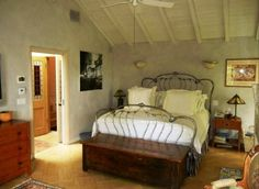An iron bed and painted white slanted ceiling are rustic and charming in Kyle MacLachlan's Los Angeles home.