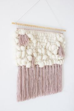 "Original hand crafted wall hanging made from exquisite fibers including merino roving and merino wool. This soft and luxurious tapestry is hand woven with beautiful hues of ivory and petal pink. The perfect addition to your gallery wall, living room, or nursery. Colours are true but please be aware that there may be differences between my monitor and yours.  Hung on a 52 cm (20,5"") wooden dowel, this weaving hangs 58 cm (23"")long from the dowel to end of fringe (longest point), and is 50 cm…"