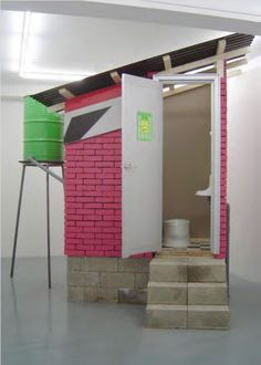 """Versión 3 de """"Caracas: Dry Toilet"""". 2003. Materiales de construcción. 2.0 x 2.7 x 3.2 mt. Galerie Nordenhake / Berlín / Stockholm / 03 marzo – 17 abril / 2004. Cortesía de la artista y Galerie Nordenhake."""