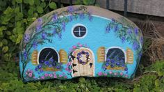 This rock house has been painted blue with yellow accents and lots of floral details. Etsy, MyPaintedSwan, sold