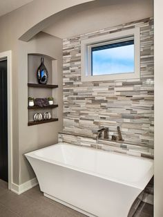 Contemporary master bathroom with a freestanding tub, beige tile, gray tile and gray walls.