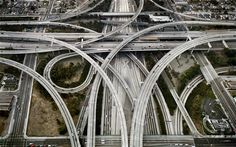 Highway #1, Intersection 105 & 110, Los Angeles, California USA, 2003 This image was the first time Edward Burtynsky utilized a helicopter to take a photograph, a technique that enabled him to develop his striking use of aerial viewpoints. Los Angeles is the home of the suburb and freeway, and owes its existence to oil and the motor industry.  Highway #1, a four layered intersection, is pictured here as a series of abstract interwoven ribbons.