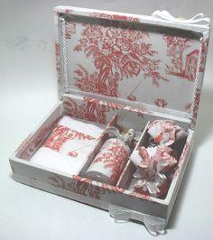 Caixa de madeira forrada em tecido com divisórias. Inclui 1 frasco de sabonete líquido com aplicação de tecido, 1 toalha da mão com aplicação de tecido e 2 sachês.