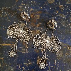 A beautiful, wide and ornate sterling silver earring made by Mazahua artisans near Mexico City. This is a very pretty traditional butterfly shaped earring with a flower at the top holding the lovely wide filagree work that features one lovebird sitting in the middle. There is a large silver filagree-shaped