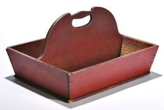 Skinner's Shaker Auction 2898M. June 4, 2016. Lot: 231.  Estimate: $800-1,200.  Realized: $1,968.  Description:  Shaker Bittersweet/red-painted Utensil Carrier, Mount Lebanon, New York, 19th century, the arched and pierced handle divides the dovetail-constructed box with canted sides, (paint wear to interior), ht. 7 3/4, wd. 13 3/8, dp. 11 in.