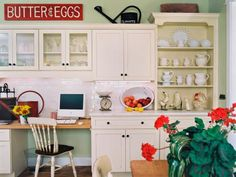 This adorable country kitchen makes the most of the space above the kitchen cabinets with a vintage watering can and colorful metal sign. Creamy cabinets and neutral dishware keep the space from looking too cluttered.