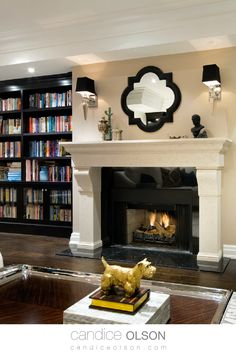 Black Library Bookcases • Ivory Stone Classic Fireplace • Sconce Lighting Above Fireplace Mantle • Library Ideas • Den Ideas • Design With Books•   #candiceolson #candiceolsondesign Stone Fireplace Mantles, Fireplace Surrounds, Fireplace Design, Fireplaces, Library Design, Library Ideas, Classic Fireplace, Candice Olson, Den Ideas
