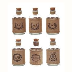 As corked accents, or as a unique bud vase or candlestick, these glass apothecary bottles inject some sweet and slightly mysterious vintage chic to your style. Rustic burlap labels bear Parisian crests of flowers and numbers, giving you a chance to mix them up or spread them around.