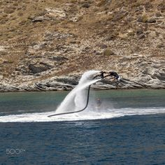 Flyboarding in Mykonos - Mykonos July 30th - Man flyboarding off the coast of Mykonos. Mykonos Greece July 30th 2016