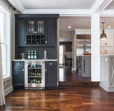 A built-in bar by Redstart Construction is painted in a charcoal gray that complements the kitchen cabinets.