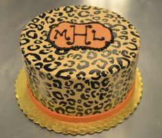 Check out this awesome orange leopard print cake topped with a monogram!